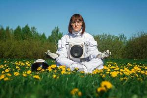 Woman astronaut sits on a green lawn in a meditative position photo