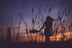 Silhouette of a girl at a meadow on background of sunset photo