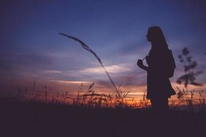 silueta de niña con una mochila en un prado en el fondo del atardecer foto