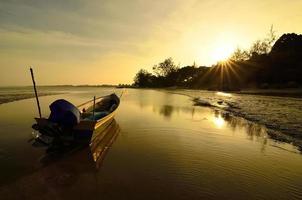 barco cerca de la playa cuando se pone el sol foto