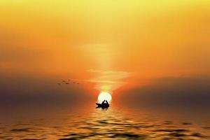 Silhouette of a couple in the boat when the sun goes down photo