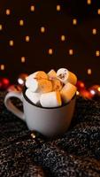Christmas hot chocolate with marshmallow with lights bokeh photo