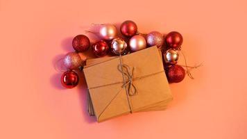 pila de cartas de papel artesanal con bolas navideñas rojas y rosas foto