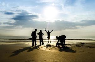 Silhouette of fishermen on the beach photo