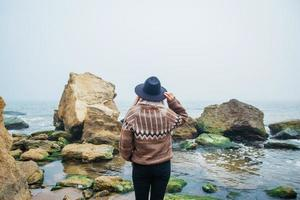Retrato de mujer joven con sombrero sobre una roca frente a un hermoso mar foto