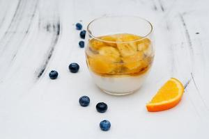 Colorful fruit jelly in a glass on a white background with blueberries photo