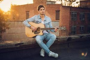 Joven tocando la guitarra en la ciudad sobre fondo de rayos de sol foto