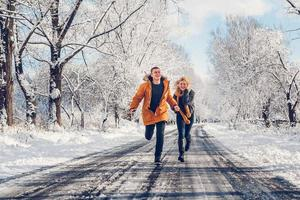 Guy and girl walk and have fun in the forest in winter photo