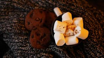 Mug with marshmallows and chocolate chip cookies photo