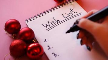 Woman writing her wish list. Festive design on pink background photo