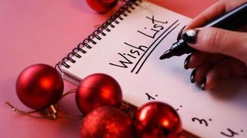 Woman writing her wish list. Festive design on pink photo