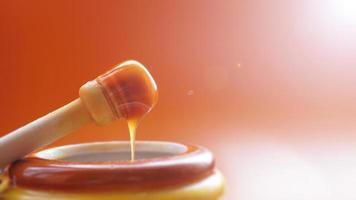 Honey dripping from honey dipper on yellow background photo