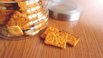 Wheat cracker in a glass jar on wooden table. photo