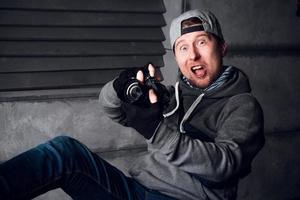 Hombre con una cámara y una cara divertida sentado en una silla en un estudio gris foto