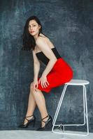 Woman wearing a red dress sitting on chair on a gray background photo