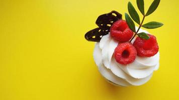 Homemade muffins with sweet cream and fresh red raspberries photo