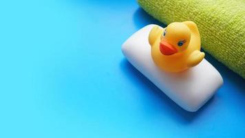 Towel, soap and yellow toy duck on a blue background photo