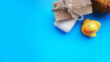 Handmade soap and yellow toy duck on a blue background photo