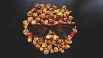 Abstract image of viewer, 3D glasses and popcorn on black background photo