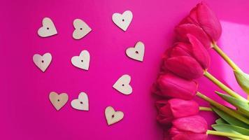 tulipanes rosas con corazones sobre fondo rosa. endecha plana, vista superior. foto