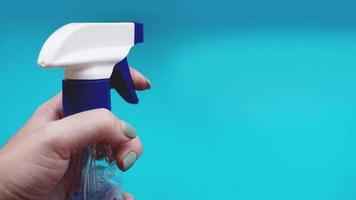 Mano femenina sosteniendo spray con detergente sobre fondo azul. foto