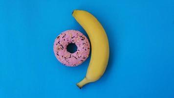 Donut dulce y plátano sobre fondo de color azul foto
