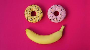 dos donas y un plátano yacen sobre una superficie rosa, formando una emoción de sonrisa foto