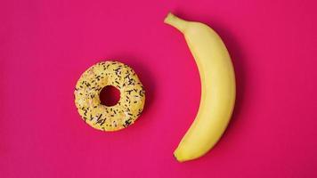 plátano amarillo y donut sobre fondo rosa. vista de arriba foto