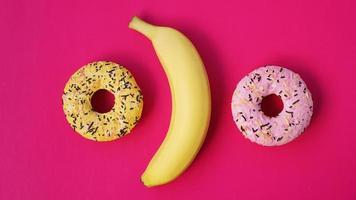 plátano amarillo y donas sobre fondo rosa. vista de arriba foto