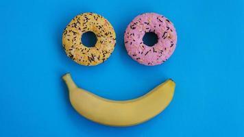 Dos donas y un plátano yacen sobre una superficie azul, formando una emoción de sonrisa foto