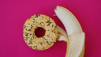Donut dulce y plátano sobre fondo de color rosa foto