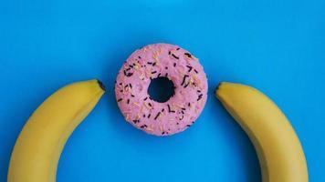 dos plátanos y un fondo azul rosquilla rosa. concepto erótico foto