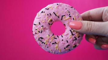 Woman holding pink donut on pink background. Pink donut in hand photo