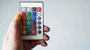 Control remoto para cambiar colores en mano aislado en blanco foto