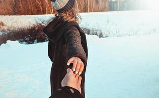 Follow me girl holding boyfriend hand in winter snow forest. photo