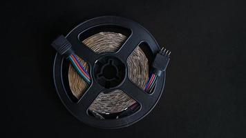 LED tape coil. LED lights tape on black. RGB-light off photo