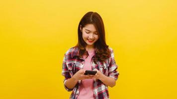 mujer asiática que usa el teléfono con expresión positiva, sonríe ampliamente. foto