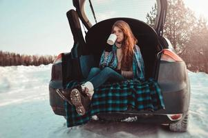 A cup of cocoa with marshmallows in hands in mitten photo