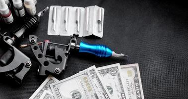 Tattoo machines on a black background and dollars. Tattoo art concept photo