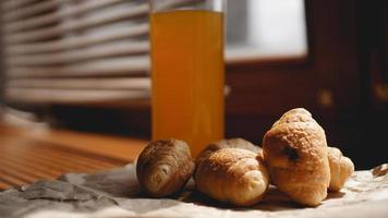 Freshly baked croissants with orange juice on kraft paper photo
