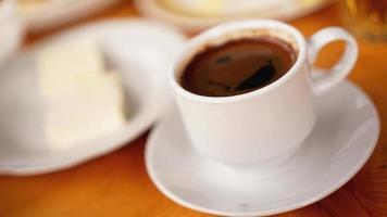 Una taza de café en una taza blanca sobre fondo de madera foto