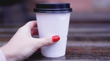 Cup of coffee on a wooden table in female hands. Paper cup Plastic cap photo