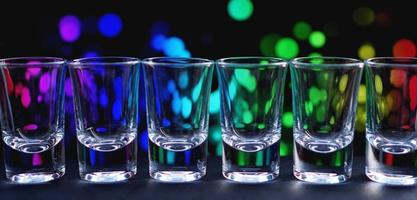 Fila de vasos limpios y brillantes en una barra de bar en una discoteca foto