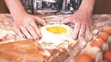 Panadero de sexo femenino profesional cocinar la masa con huevos y harina foto