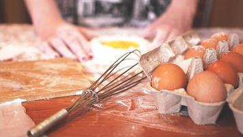 Professional female baker cooking dough with eggs and flour photo
