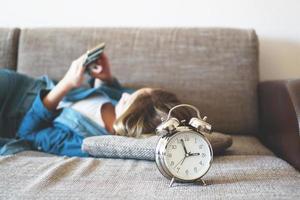 mujer joven, utilizar, teléfono, en cama, mirar la pantalla foto