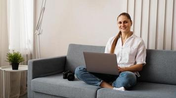 Happy young woman using laptop at home photo