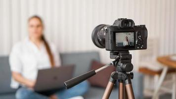 Blogger recording video indoors, selective focus on camera display photo