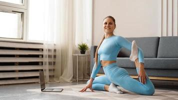 Beautiful young woman doing fitness exercise at home with her laptop photo