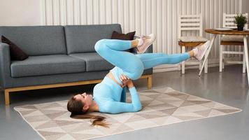 Young determined confident slim woman doing exercises at home photo